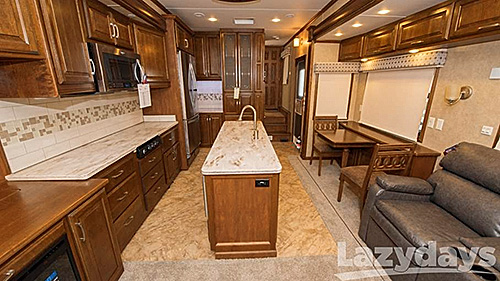 The living and kitchen area as roominess to make families and friends feel comfortable while traveling in the 2016 DRV Mobile Suites Fifth Wheel.